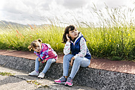 Two little sisters sitting on curb looking at distance - MGOF001939
