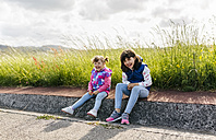 Two laughing little sisters sitting at roadside - MGOF001942