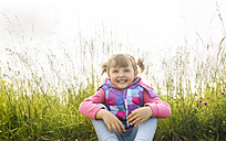 Happy little girl sitting in front of a meadow - MGOF001945