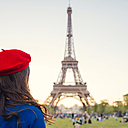 France, Paris, Champ de Mars, back view of woman wearing red beret looking at Eiffel Tower - GEMF000919