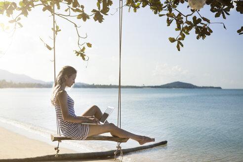 Thailand, woman using laptop on beach - SBOF000001