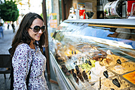 Woman looking at ice cream in an ice cream shop showcase - KIJF000404
