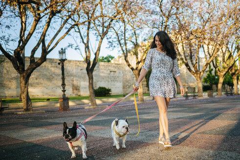 Woman walking her two dogs - KIJF000416