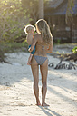 Thailand, mother carrying son on sandy beach - SBOF000044