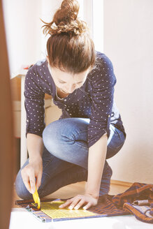 Young woman cutting fabric on the floor at home - SEGF000575