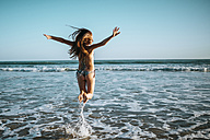 Enthusiastic young woman jumping on beach - KIJF000423