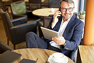 Portrait of smiling businessman with digital tablet sitting in a cafe telephoning with smartphone - MAEF011820