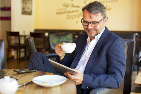 Portrait of smiling businessman using digital tablet while sitting in a cafe drinking coffee - MAEF011823