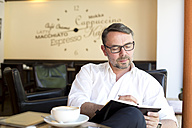 Portrait of businessman sitting in a coffee shop with notebook writing down something - MAEF011829