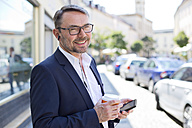 Portrait of smiling businessman with coffee to wearing earphones - MAEF011832
