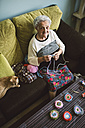 Portrait of crocheting senior woman sitting on couch beside her sleeping cat - RAEF001205