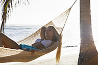 Dominican Rebublic, Young woman lying in hammock on tropical beach - HSIF000462