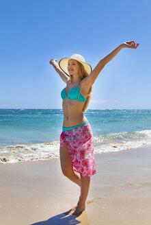 Dominican Rebublic, Young woman walking along tropical beach - HSIF000468