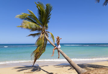 Dominican Rebublic, Young woman climbing palm tree at tropical beach - HSIF000471