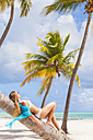 Dominican Rebublic, Young woman relaxing on palm tree looking out over tropical beach - HSIF000477
