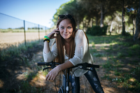 Smiling young woman with bicycle in rural landscape - KIJF000479