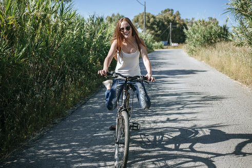 Happy young woman riding bicycle on country lane - KIJF000482
