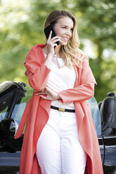 Portrait of smiling blond woman telephoning with smartphone in front of black sports car - GDF001010
