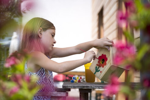 Girl painting red flower on a birdhouse - SARF002771