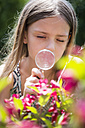 Portrait of girl looking using magnifying glass in the garden - SARF002774