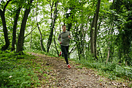 Young man running in forest - ZEDF000199