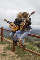 Two women sitting on wooden fence playing guitar - JPF000158