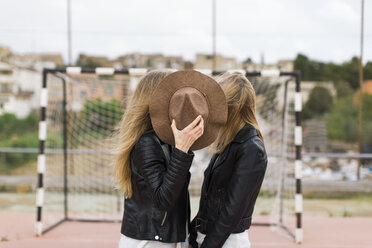 Two women standing on sports field covered with hat - JPF000164