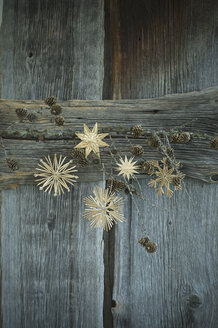 Larch twig and straw stars hanging on wooden wall - ASF005902