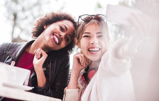 Two best friends taking selfie with smartphone - UUF007645