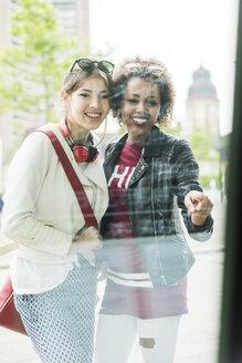 Two young women looking in shop window - UUF007648