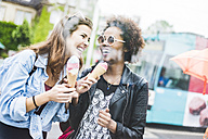 Two laughing women with icecream cones - UUF007666