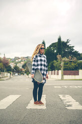 Smiling young woman with skateboard on the street - DAPF000123