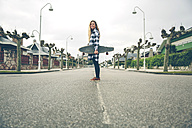 Smiling young woman with skateboard on the street - DAPF000129