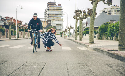 Happy couple with bicycle and skateboard on the street - DAPF000132
