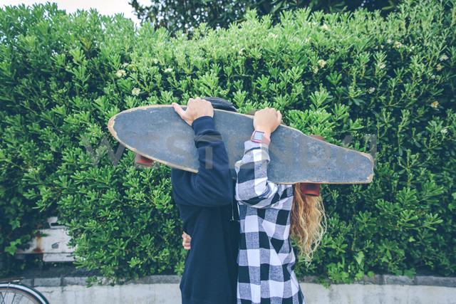 Couple hiding behind skateboard - DAPF000135