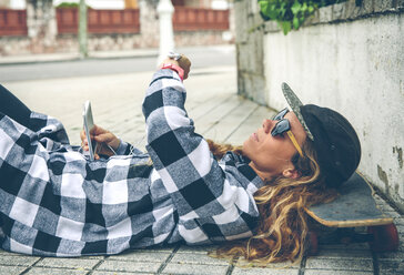 Young woman lying on skateboard looking at smartwatch - DAPF000144