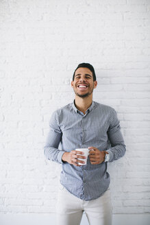 Young businessman standing against wall, holding cup up coffee - EBSF001452