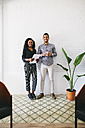 two young business people standing against wall, haolding papers and cup of coffee - EBSF001455