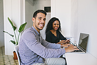 Young businessman and woman working together in office, using laptop - EBSF001467