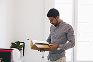Young man in office reading files - EBSF001476