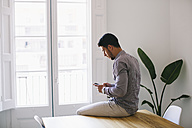Young businessman sitting on desk using smart phone - EBSF001485