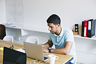 Young man working in office, using laptop - EBSF001491