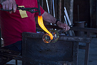 Man working with molten glass in a glass factory - ABZF000680