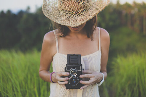 Woman with old camera in fields - KNTF000342