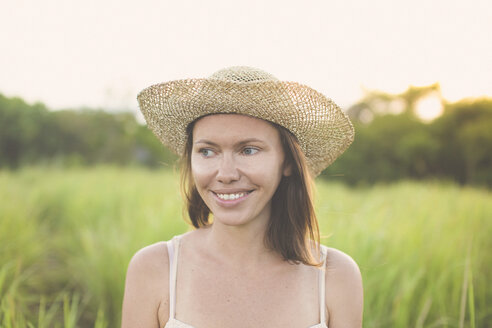 Portrait of smiling woman wearing summer hat in nature - KNTF000345