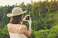 Back view of woman taking picture with smartphone in nature - KNTF000348