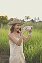 Smiling woman taking picture with smartphone in nature - KNTF000351