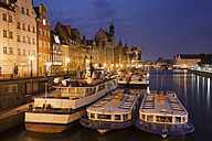 Poland, Gdansk, view to the Old Town by night with moored tourboats in the foreground - ABOF000088