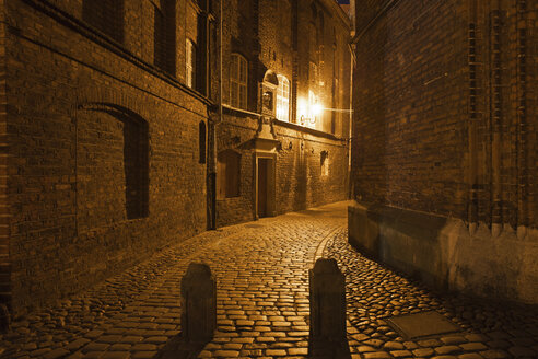 Poland, Gdansk, paved dark alley in historic city centre by night - ABOF000091