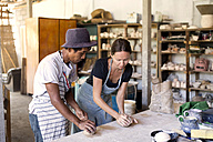 Man and woman in workshop working on pottery - KNTF000352